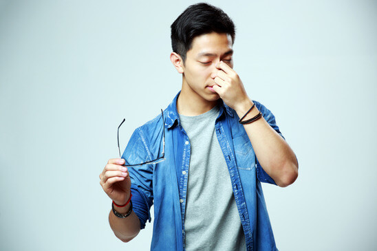 Asian man holding glasses and rubbing his eyes on gray background